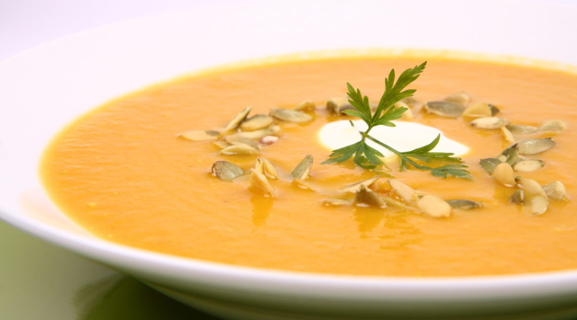 Pumpkin soup decorated with cream, pumpkin seeds and parsley